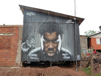 O grafite está na parede de uma casa de madeira (Foto: Lucas Marques / ON)
