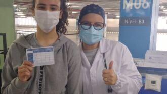 Isadora, na expectativa pela segunda dose, exibe o comprovante da vacina (Foto: Divulgação/SES)
