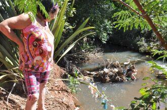 Moradora observa a cerca de arame que antes ficava quase dois metros de distância da água