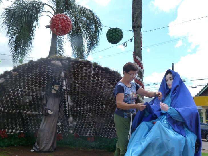Voluntária ajusta últimos detalhes na decoração natalina exposta na Praça Miguel Moretti (Foto: Claudia Dalmuth/ON)