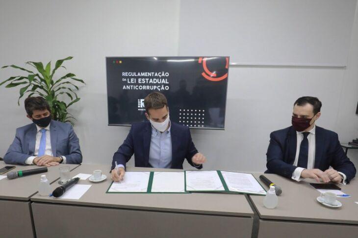 Leite assina decreto ao lado do deputado Tiago Simon (E), autor da proposta, e do procurador-geral Eduardo Cunha da Costa (D) (Foto: Itamar Aguiar/Palácio Piratini)