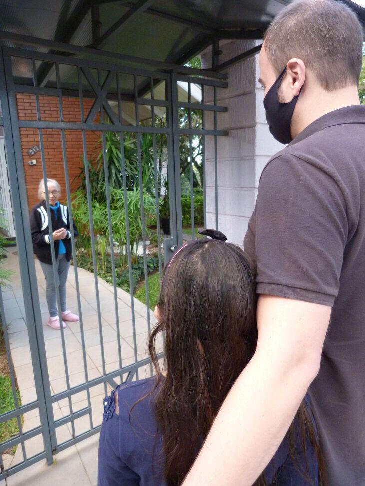 Familiares conversam com idosos do lado de fora da instituição, através do portão (Foto: Bruna Scheifler/ON)