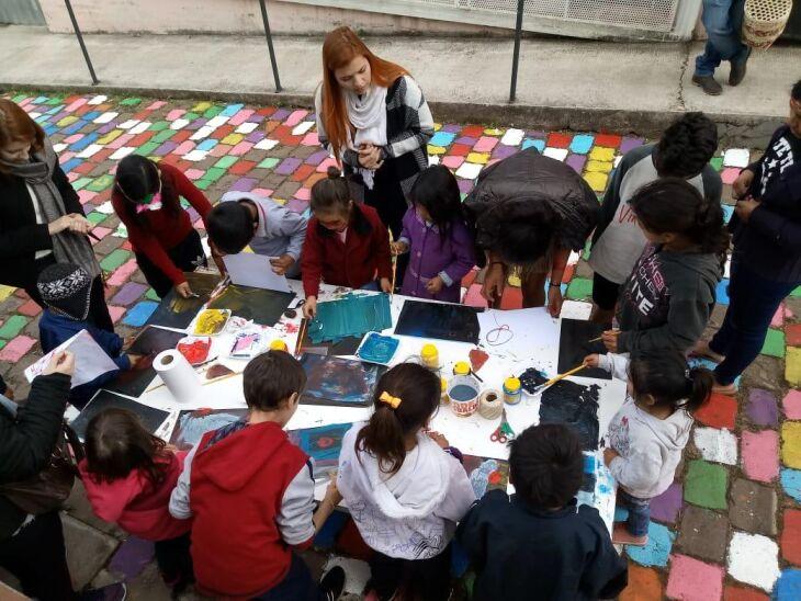 Grupo de crianças pintando em uma das atividades