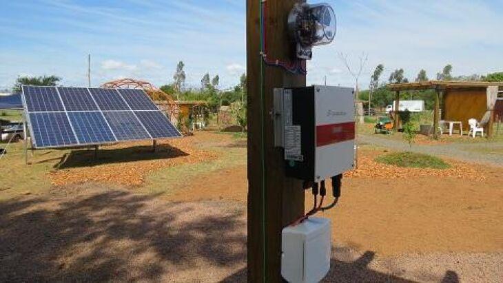 Demonstração de sistema gerando energia por meio de um conjunto de placas ligadas a um inversor e suas conexões